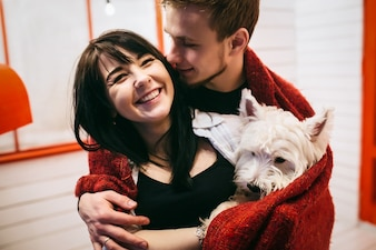 Cheerful couple cuddling with dog in plaid