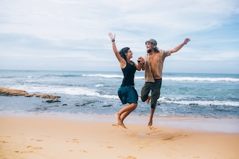 Cheerful couple jumping on sand