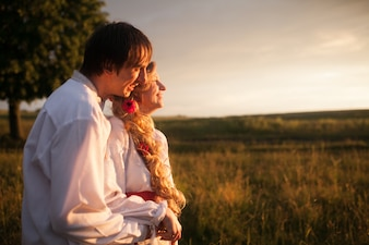 Cheerful couple posing in field