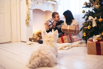 Cheerful couple with dog opening presents