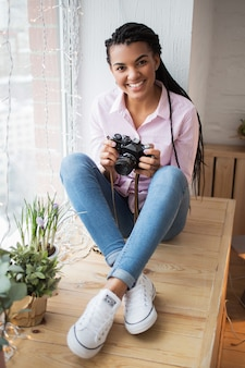 Cheerful female photographer looking at camera