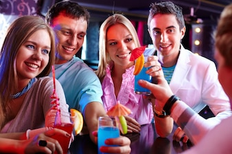 Cheerful friends holding cocktails