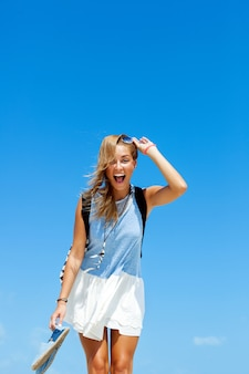 Cheerful girl laughing and holding her sandals