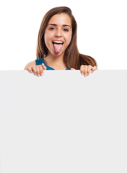 Cheerful girl showing her tongue and holding an empty sign