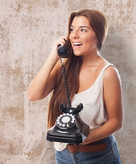Cheerful girl with landline phone
