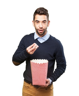 Cheerful guy eating popcorn