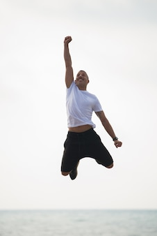 Cheerful guy feeling power and energy in mid-air