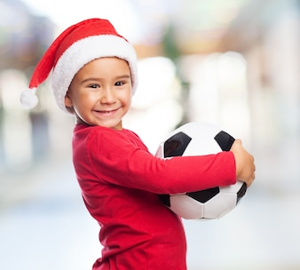 Cheerful kid holding his ball with blurred background