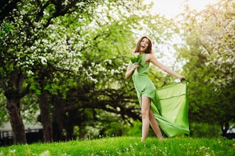Cheerful lady jumps in green garden