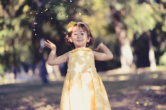 Cheerful little girl playing with confetti