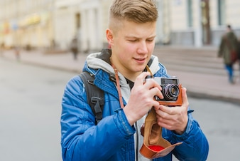 Cheerful man standing with camera