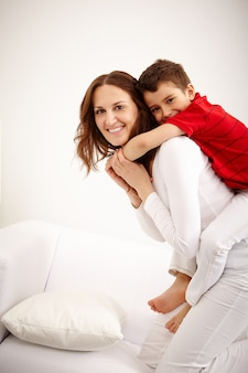 Cheerful mother carrying little boy on her back