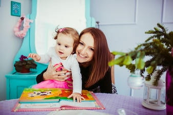 Cheerful mother hugs from behind her little daughter sitting at