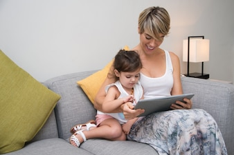 Cheerful mother showing game on tablet to daughter