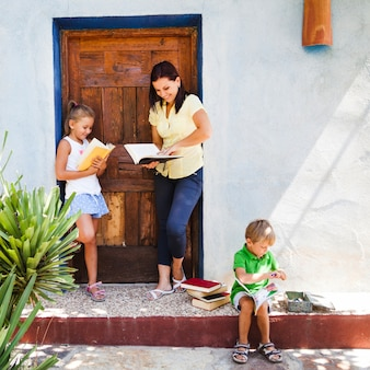 Cheerful mother with kids on porch