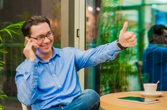 Cheerful relaxed young businessman showing ok gesture and talking on cell phone in cafe