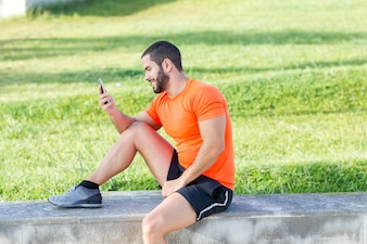 Cheerful runner using phone to analyze his results