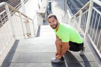 Cheerful sportsman tying shoelaces on sneakers