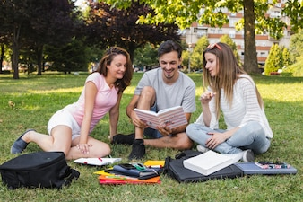 Cheerful students reading book