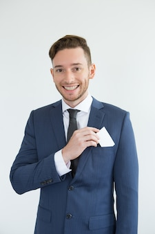 Cheerful successful handsome businessman with card