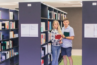 Cheerful teens with books in library
