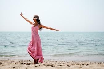 Cheerful woman dancing on the beach