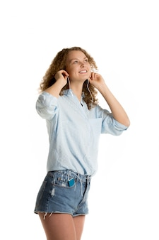 Cheerful woman in shorts listening to music