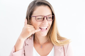 Cheerful woman showing call gesture and winking