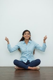 Cheerful Woman Sitting on Floor and Pumping Fists