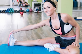 Cheerful woman stretching on mat