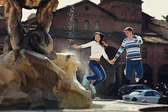 Cheerful young couple jumps before fountain somewhere in Rome