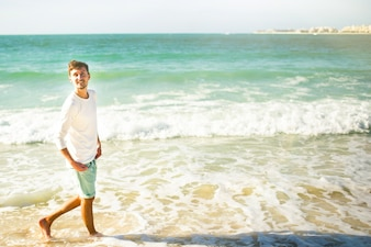 Cheerful young man looks up in the sky walking in foaming waves