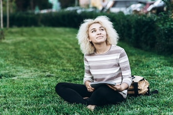 Cheerful young student girl sits on a grass in campus