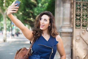 Cheerful young woman taking selfie outdoors