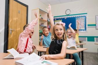 Cheering schoolkids in classroom raising hands
