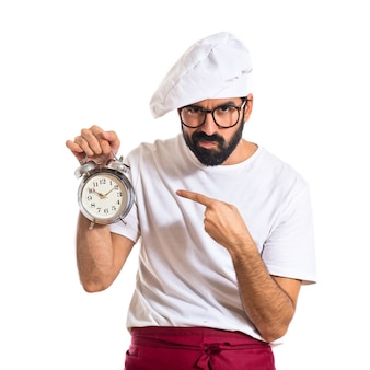 Chef holding a clock over white background