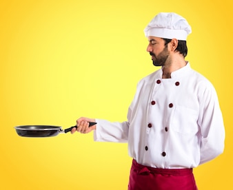 Chef holding frying pan on colorful background