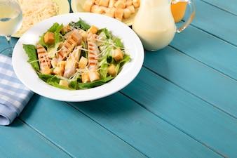 Chicken caesar salad on blue picnic table