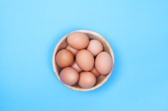 Chicken egg in wood bowl on blue background with space for copy .
