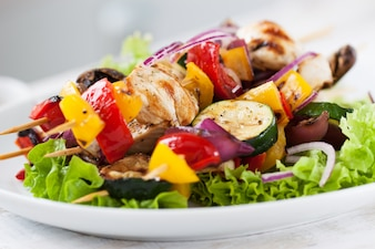 Chicken skewers with onions on top of a salad