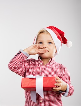 Child covering her mouth with one hand and in the other a gift