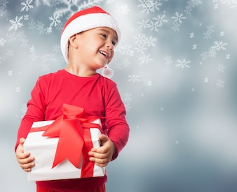 Child holding a white gift in a snowflakes background