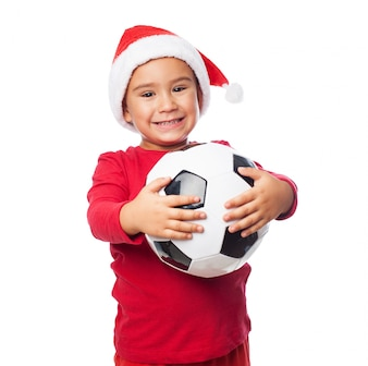 Child holding his ball with a big smile