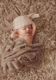 Child in hat like rabbit ears sleeps on fluffy carpet