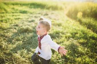 Child running happily by the field