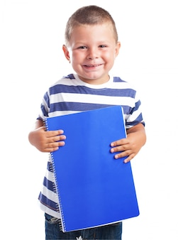 Child smiling with a blue notebook