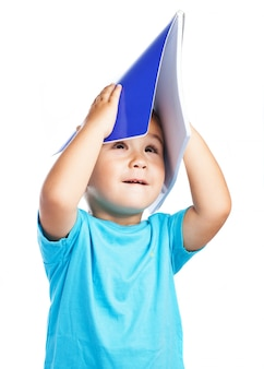 Child using a notebook as a hat