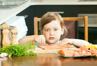 Child with raw salmon fish  in  kitchen