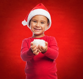 Child with santa's hat and snow in his hands