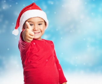 Child with thumb up in snow background